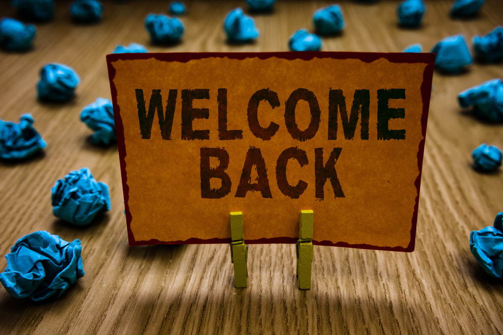 Conceptual hand writing showing Welcome Back. Business photo text Warm Greetings Arrived Repeat Gladly Accepted Pleased Clothespins holding orange paper note crumpled papers mistake